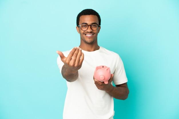 Afroamerykanin przystojny mężczyzna trzyma skarbonkę na pojedyncze niebieskim tle zapraszając do przyjścia z ręką. cieszę się, że przyszedłeś