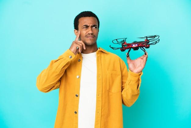 Afroamerykanin, przystojny mężczyzna, trzymający drona na odosobnionym niebieskim tle, mający wątpliwości i myślący