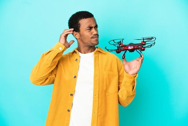 Afroamerykanin, przystojny mężczyzna, trzymający drona na odosobnionym niebieskim tle, mający wątpliwości