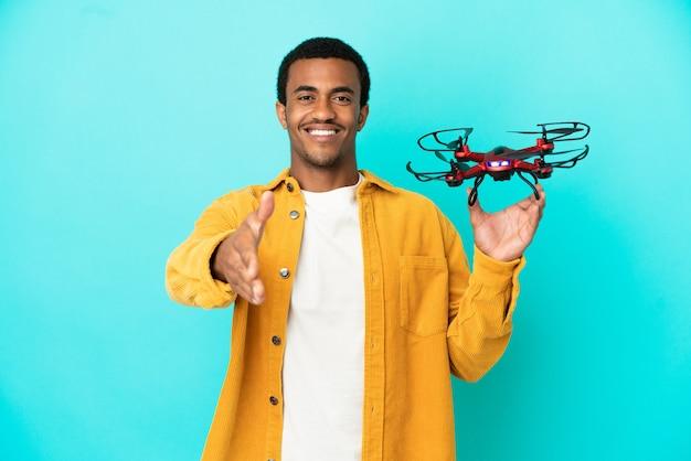 Afroamerykanin, przystojny mężczyzna, trzymający drona na odosobnionym niebieskim tle, ściskający dłonie, by zamknąć dobrą ofertę