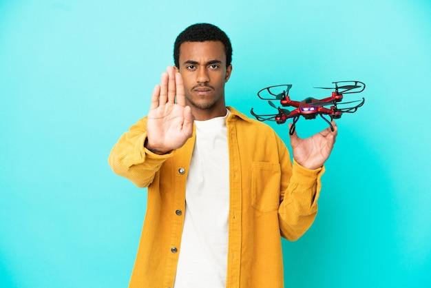 Afroamerykanin, przystojny mężczyzna, trzymający drona na odosobnionym niebieskim tle, wykonujący gest zatrzymania
