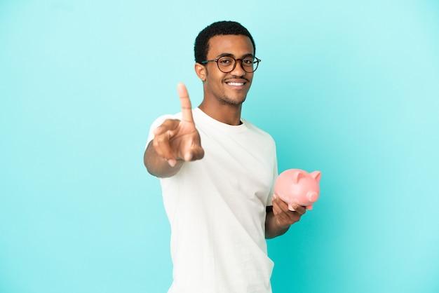 Afroamerykanin, przystojny mężczyzna, trzymający skarbonkę na białym tle, pokazujący i unoszący palec