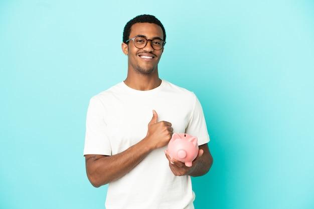 Afroamerykanin, przystojny mężczyzna, trzymający skarbonkę na odosobnionym niebieskim tle, dumny i zadowolony z siebie