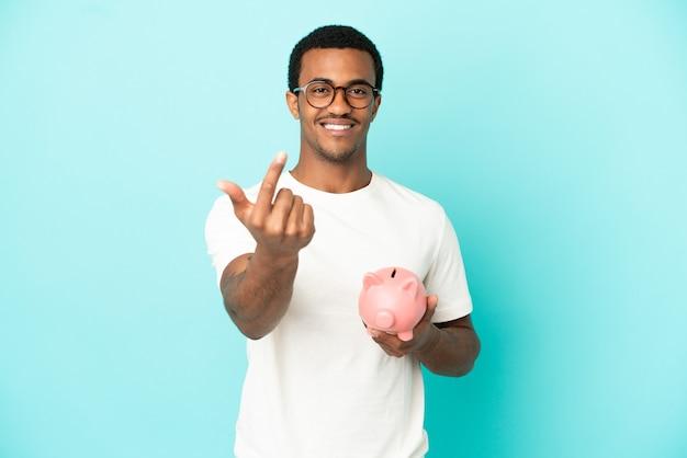 Afroamerykanin, przystojny mężczyzna, trzymający skarbonkę nad odosobnionym niebieskim tłem, wykonujący nadchodzący gest