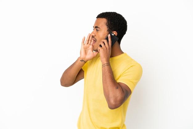 Afroamerykanin, przystojny mężczyzna, używający telefonu komórkowego na białym tle, krzycząc z szeroko otwartymi ustami