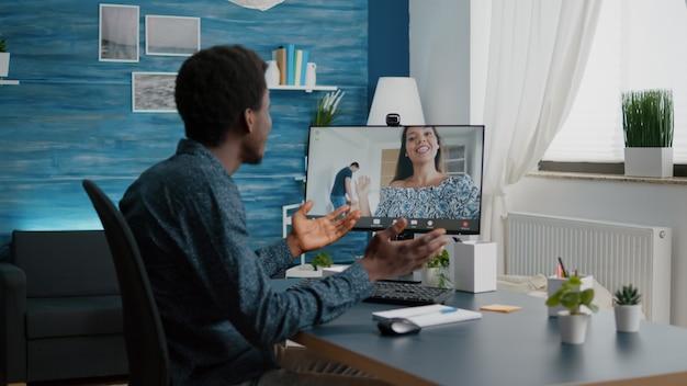 Afroamerykanin rozmawia przez wideorozmowę online z przyjaciółmi i rodziną za pomocą kamery internetowej...