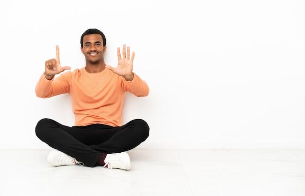Afroamerykanin siedzący na podłodze na białym tle copyspace liczący siedem palcami