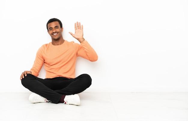 Afroamerykanin siedzący na podłodze na białym tle copyspace pozdrawiając ręką z szczęśliwym wyrazem twarzy