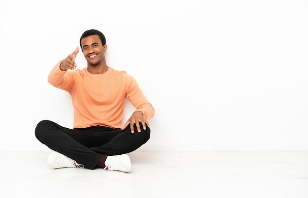 Afroamerykanin siedzi na podłodze na białym tle copyspace, ściskając ręce, aby zamknąć dobrą ofertę