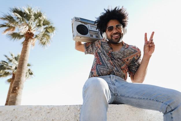 Afroamerykanin słuchanie muzyki z rocznika stereo boombox na świeżym powietrzu na plaży - letni styl życia, koncepcja podróży i imprez - skoncentruj się na twarzy