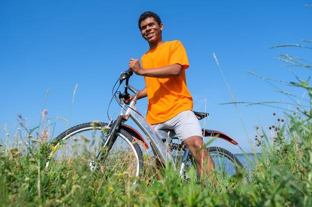 Afroamerykanin stojący z rowerem na łące na tle błękitnego nieba