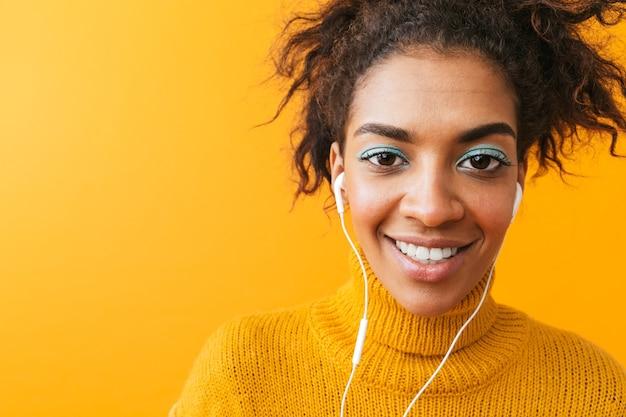 Afroamerykanin szczery kobieta w ubranie, słuchanie muzyki przez białe słuchawki, na białym tle