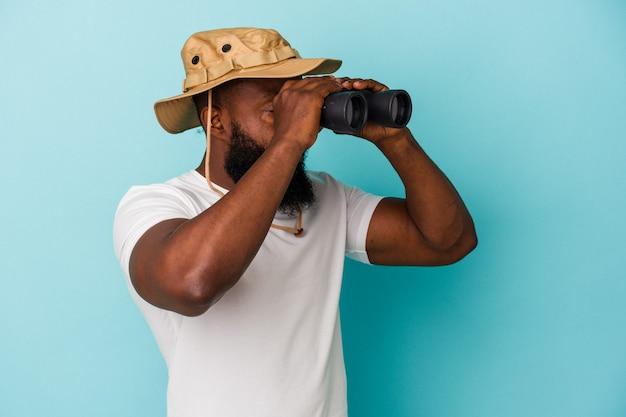 Afroamerykanin trzymający lornetkę odizolowaną na niebieskiej ścianie