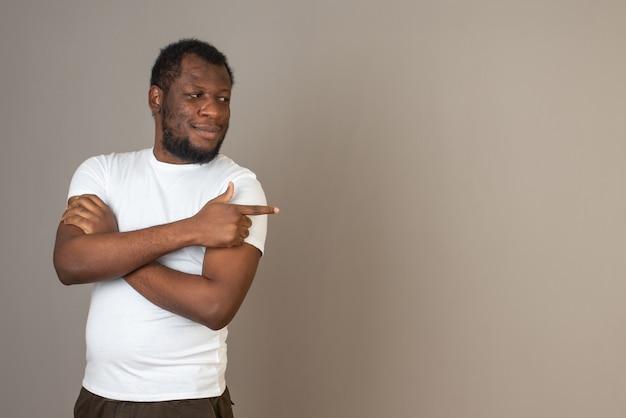 Afroamerykanin, trzymający założone ręce, wskazując jedną ręką w lewo, stojący przed szarą ścianą.