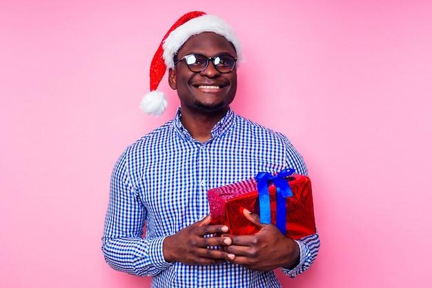 Afroamerykanin ubrany w stylową koszulę w kratę, wielki uśmiech w santa hat z pudełkiem na różowym tle studio.ciemnoskóry święty mikołaj gratulujący wesołych świąt