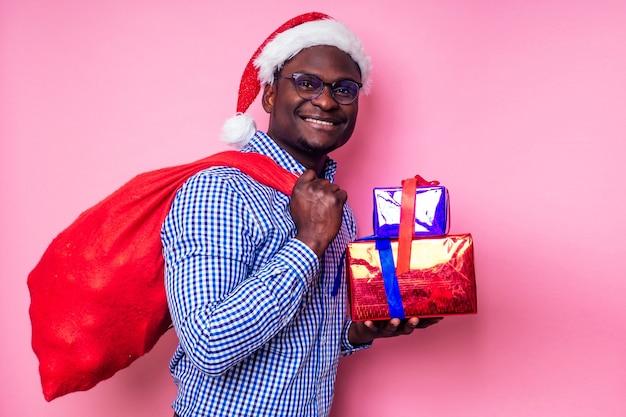 Afroamerykanin ubrany w stylową koszulę w kratę wielki uśmiech w santa hat z pudełkiem na różowym tle studio.ciemnoskóry święty mikołaj wesołych świąt z workiem pełnym świątecznych gadżetów.
