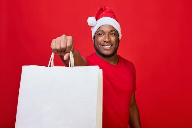 Afroamerykanin uśmiecha się w kapeluszu świętego mikołaja i trzyma białe papierowe torby na czerwonym tle