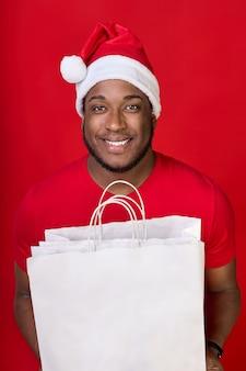 Afroamerykanin uśmiecha się w kapeluszu świętego mikołaja i trzyma w rękach białe papierowe torby na czerwonym tle