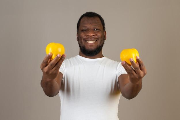 Afroamerykanin uśmiechnięty mężczyzna z pigwą w obu rękach, stojący przed szarą ścianą.