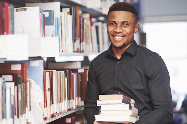 Afroamerykanin w bibliotece, szukając informacji w książkach