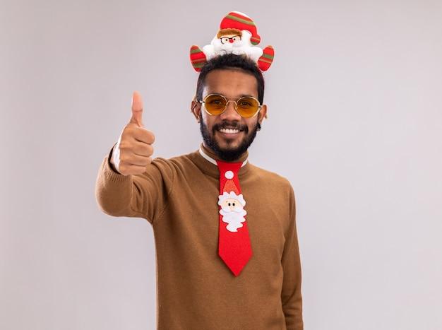 Afroamerykanin w brązowym swetrze i obręczy mikołaja na głowie z zabawnym czerwonym krawatem patrząc na kamerę uśmiechnięty wesoło, pokazując kciuki do góry stojąc na białym tle