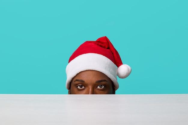 Afroamerykanin w czapce świętego mikołaja spogląda spod stołu prosto w kamerę