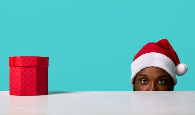 Afroamerykanin w kapeluszu świętego mikołaja patrzy na kamerę spod białego stołu