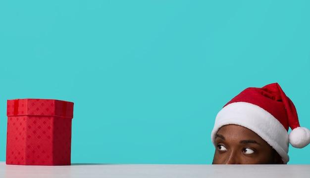 Afroamerykanin w kapeluszu świętego mikołaja patrzy na prezent spod stołu