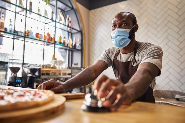 Afroamerykanin w ochronnej masce na twarz używający dzwonka stojącego przy ladzie ze świeżo upieczoną pizzą