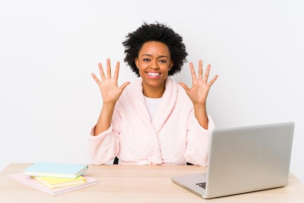 Afroamerykanin w średnim wieku kobieta pracuje w domu na białym tle pokazuje numer dziesięć rękami.