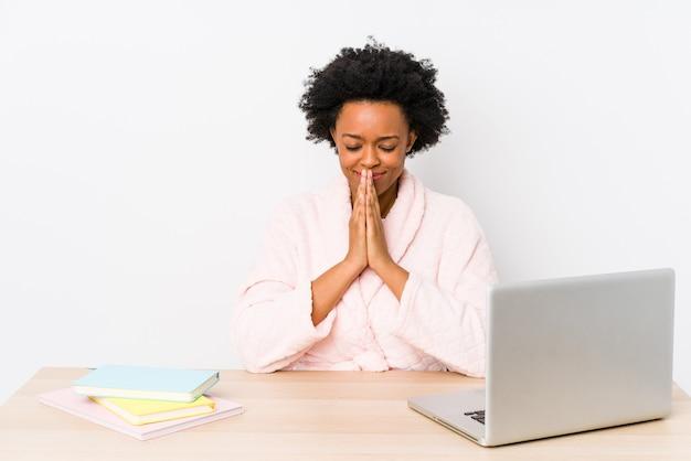 Afroamerykanin w średnim wieku pracujący w domu na białym tle trzymając się za ręce w módlcie się w pobliżu ust, czuje się pewnie.