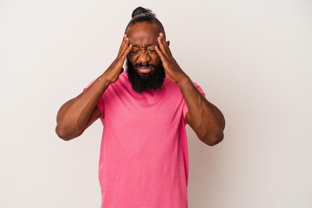 Afroamerykanin z brodą na białym tle na różowym tle dotyka świątyń i ma ból głowy.