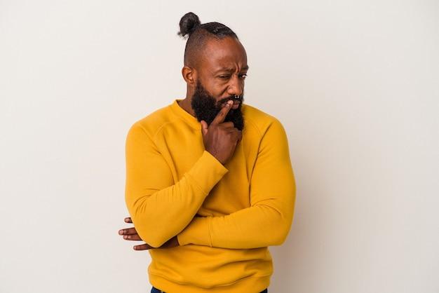 Afroamerykanin z brodą na białym tle na różowym tle kontemplując, planując strategię, myśląc o sposobie prowadzenia biznesu.
