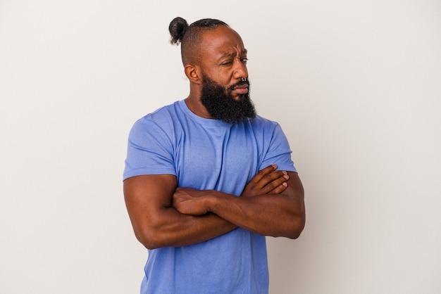 Afroamerykanin z brodą na białym tle na różowym tle podejrzany, niepewny, bada cię.