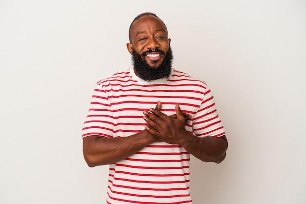 Afroamerykanin z brodą wyizolowaną na różowym tle ma przyjazny wyraz twarzy, przyciskając dłoń do klatki piersiowej. koncepcja miłości.