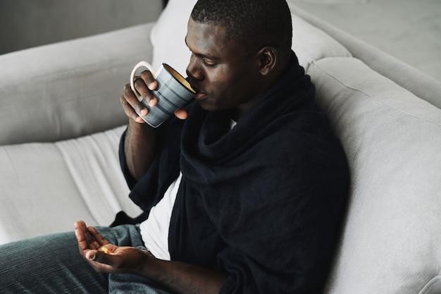 Afroamerykanin z kubkiem w dłoni siedzi na sofie, widok z góry