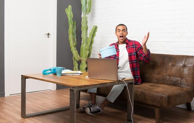 Afroamerykanin z laptopem w salonie zaskoczony, ponieważ otrzymał prezent