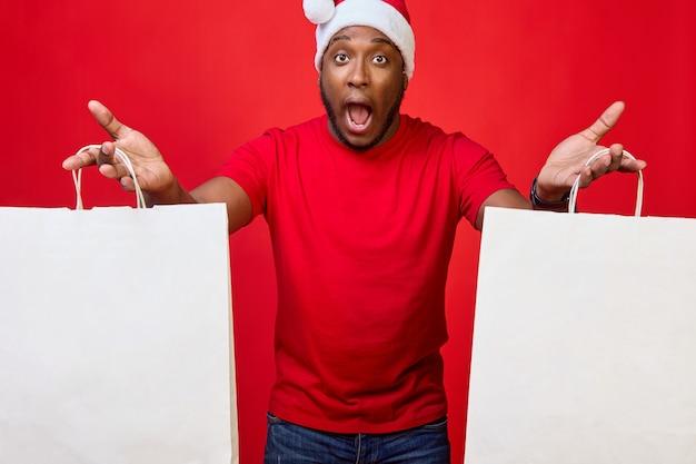 Afroamerykanin z otwartymi ustami w kapeluszu świętego mikołaja trzyma w rękach papierowe torby