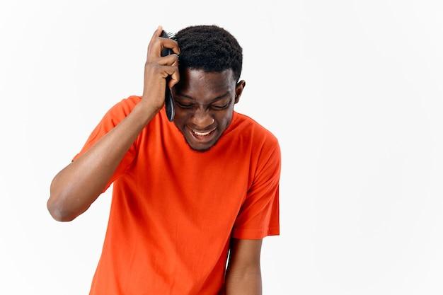 Afroamerykanin z zamkniętymi oczami czesającymi włosy pomarańczowy tshirt