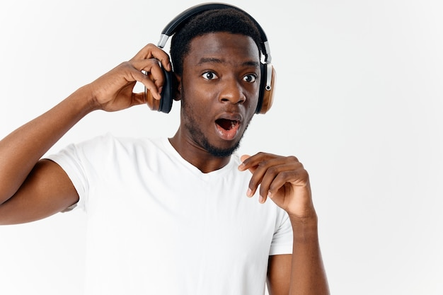 Afroamerykanin z zaskoczonym wyrazem twarzy w słuchawkach słuchających muzyki