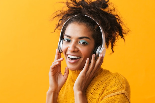 Afroamerykanin zadowolony kobieta w ubranie, słuchanie muzyki przez białe słuchawki, na białym tle
