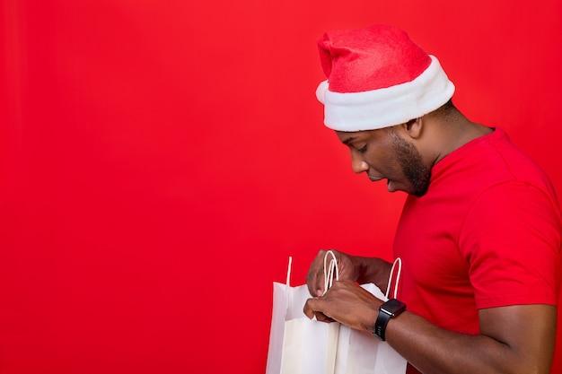 Afroamerykanin zagląda do białych papierowych toreb i przygląda się zakupom na czerwonym tle