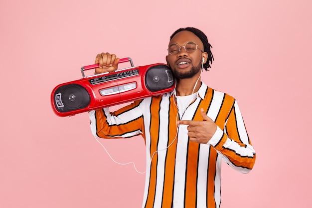 Afroamerykanin zamyka oczy i cieszy się słuchaniem muzyki w słuchawkach z magnetofonu