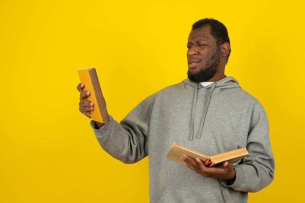 Afroamerykanin zerkając książkę w ręku, stoi nad żółtą ścianą.