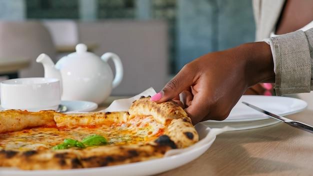 Afroamerykanka bierze kawałek smacznej świeżej gorącej pizzy z serem z tacy i herbaty, jedząc lunch w lekkim, współczesnym zbliżeniu kawiarni