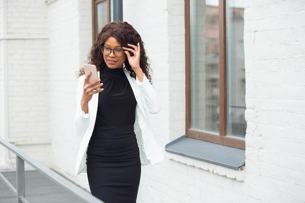 Afroamerykanka bizneswoman w stroju biurowym za pomocą smartfona