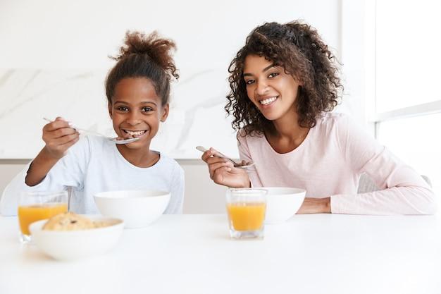 Afroamerykanka i jej mała córka jedzą śniadanie i jedzą płatki kukurydziane w kuchni