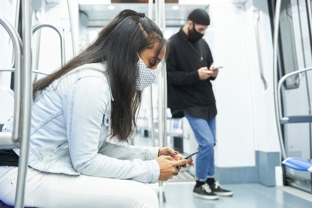 Afroamerykanka i kaukaski chłopiec korzystający ze smartfona w wagonie metra.