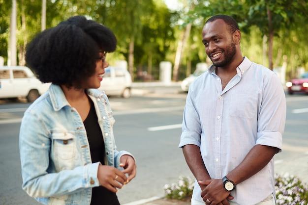 Afroamerykanka i murzyn rozmawiają o wiadomościach, stojąc na miejskiej ulicy.