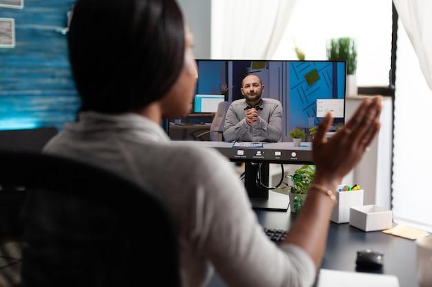 Afroamerykanka korzysta z uniwersyteckiej platformy e-learningowej, rozmawiając ze zdalnym koleg...